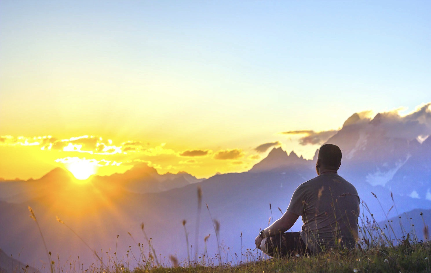 man sitting on grass at sunset in mountains thinking and looking on sun